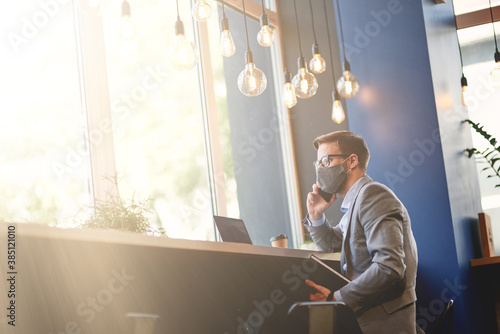 Fototapeta Work during covid 19 outbreak. Side view of a young businessman wearing protective face mask talking by phone while working remotely in cafe obraz