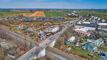 Aerial View Of An Amish Mud Sale With Lots Of Buggies And Farm Equipment
