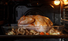 Seasoned Chicken With Vegetables In Baking Dish Cooking In Oven With Light