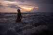 Woman going into sea at twilight