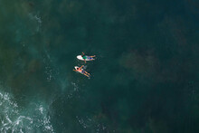 Two Surfers Paddle Towards The Waves