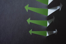 Paper Arrows Stand Up To Reveal Green Background.