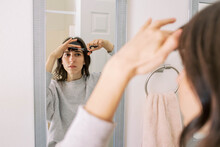 Young Woman Cutting Bangs In Mirror At Home