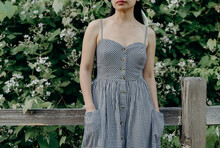 Brunette Woman In A Gingham Dress Standing By A Fence With Apple Trees Blossoming Portland, Oregon