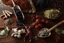 Mixed Spices, Safflower (Carthamus Tinctorius), Lavender (Lavandula Angustifolia), Rosebuds (Rosa), Cinnamon, Juniper (Juniperus), Mini-Peppers (capsicum), Chamomile (Matricaria Chamomilla), Bay (Laurus Nobilis), Ginger (Zingiber Officinale ), Sage (Salvia Officinalis) And Coriander (Coriandrum Sativum) On A Wooden Surface