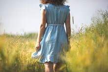 Woman In Blue Dress Walking In...