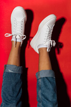 Woman With Feet Up Wearing White Sneakers Against Red Background