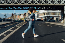 Carefree Young Woman With Afro Hair Running On Street In City During Sunny Day