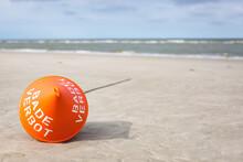 Red Buoy Lying On Beach Sand