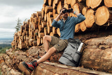 Man Looking Through Binoculars While Sitting On Log Against Woodpile In Forest