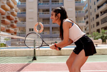 Woman Playing Tennis Against Buildings In Court On Sunny Day