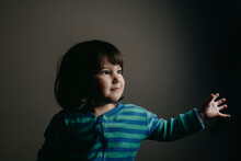 Cute Baby Girl Looking Away While Standing Against Gray Wall At Home