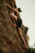 Determinant Woman Climbing Rock Mountain In Forest