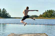 Redhead Boy Jumping Into Lake Against Clear Sky