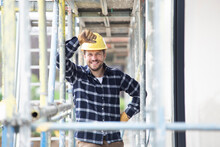 Smiling Construction Worker Wearing Helmet Standing By Scaffold At Construction Site
