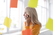 Businesswoman Talking Over Smart Phone In Home Office Seen Through Window