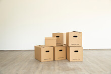 Cardboard Boxes On Floor Against White Wall In New House