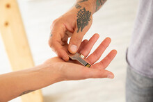 Close-up Of Man Hand Giving USB Key To Wife In New House