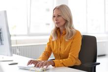 Confident Businesswoman Using ...