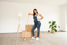 Pregnant Woman With Broom Standing By Boxes In New Unfurnished House