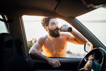 Shirtless Bearded Man Drinking...