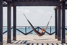 Relaxed Woman Lying In Hammock Hanging From Metallic Structure On Boardwalk