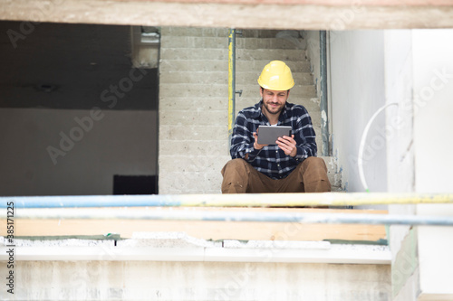 Fotografia Construction worker using digital tablet while sitting on steps at construction
