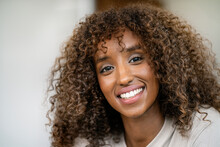 Close-up Of Smiling Female Entrepreneur With Curly Hair In Office
