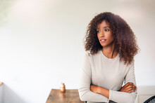 Thoughtful Businesswoman With Curly Hair Standing Against White Wall In Office