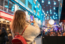 Young Woman Photographing Illuminated Christmas Lights Hanging In City At Night