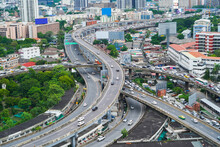 Aerial View Of Busy Cars With Traffic Jam In The Rush Hour On Highway Road Street On Bridge In Bangkok Downtown, Urban City In Asia, Thailand At Sunset. Intersection Junction. Toll Gate In Rama 9