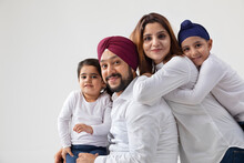 A HAPPY SIKH FAMILY POSING TOGETHER