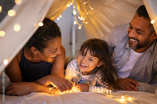 Fotomural Happy ethnic family playing together in cozy hut with daughter