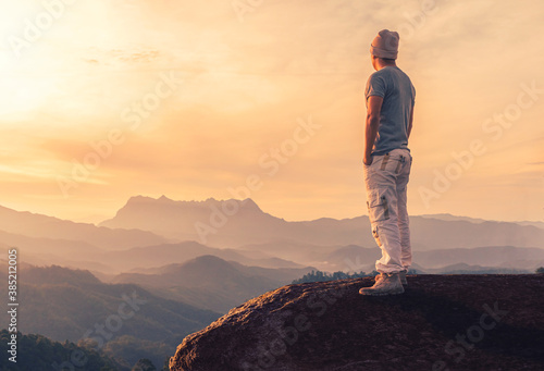 Young man standing on rock while admiring view in mountains at sunset Canvas Print