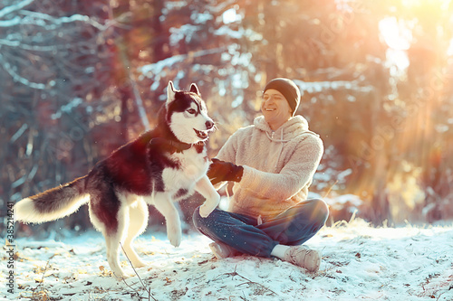 Cuadros en Lienzo young man hugs a husky dog in the winter in the forest, a man and a dog hug toge