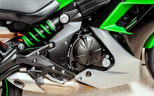 Black Engine Of Motorcycle Close-up. Sport Green Bike, Side View. Motorcycle Internal Combustion Engine With Cylinder, Shock Absorber, Exhaust Pipe, Engine Air Cooling System, Wheels And Seat.