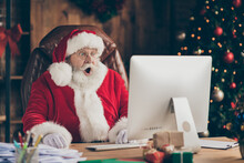 Photo Of Amazed Santa Claus Sit Table Desk Work Computer Impressed Many Wish Gift List Letters In House Idnoors With Evergreen Christmas X-mas Tree Ornament Decoration Wear Cap Headwear