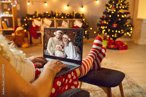 Obraz Relaxed Santa with laptop having online video call with happy family on Christmas Day - fototapety do salonu