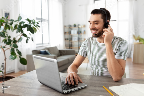remote job, technology and people concept - happy smiling man with headset and laptop computer having video conference at home office