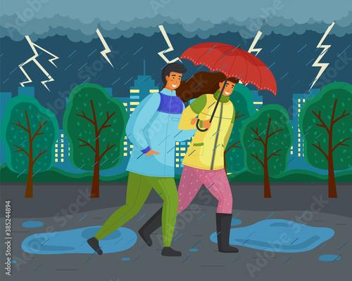 Obraz Family walks in autumn park. Girl in yellow puffer jacket, guy wears blue windbreaker, carries red umbrella. Fall landscape, lightning, ominous atmosphere. Dark landscape. Terrible lousy weather - fototapety do salonu
