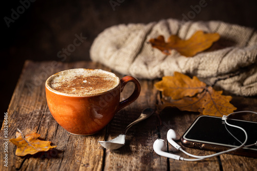 Cozy background with cup of coffee, headphones and Autumn leaves on wooden background