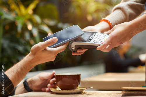 Fototapety, obrazy: Close-up of man paying online with mobile phone for his order in cafe