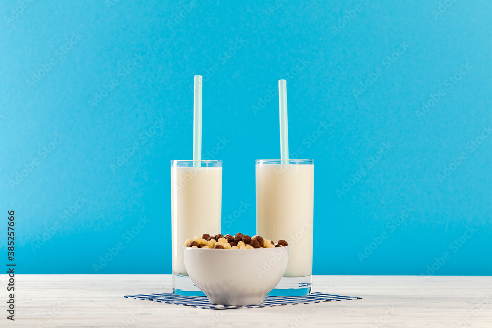 Fototapeta Breakfast cereal balls and milk in glass against blue background