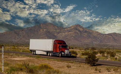 Fototapeta Classic big rig heavy duty long haul diesel semi truck with refrigerator semi trailer running on the road along mountains obraz