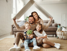 Concept Housing  Young Family. Mother Father And Children Under Fake Roof In  New Home.