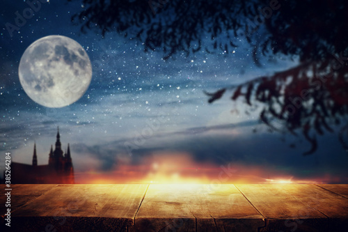 Obraz Halloween Holiday concept. Empty rustic table in front of scary and misty night sky, forest and full moon background. Ready for product display montage - fototapety do salonu