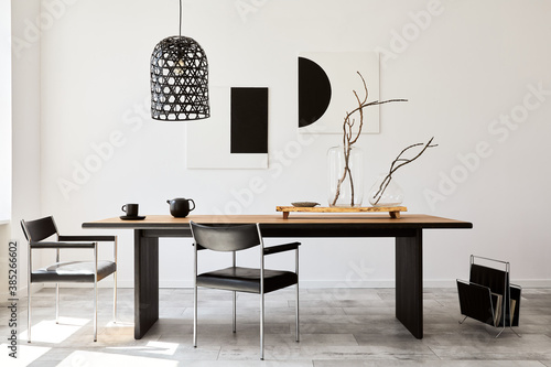 Obraz Stylish dining room interior with design wooden family table, black chairs, teapot with mug, mock up art paintings on the wall and elegant accessories in modern home decor. Template. - fototapety do salonu