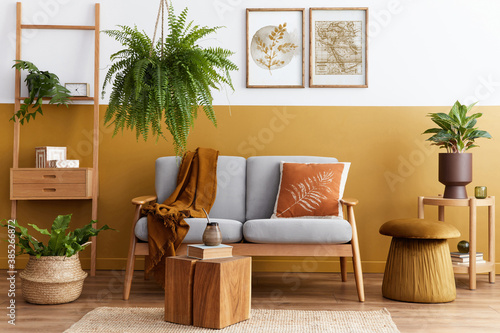 Stylish scandinavian interior of living room with design grey velvet sofa, cube, furniture, plants, carpet, decoration and mock up poster frames. Template. - 385266872