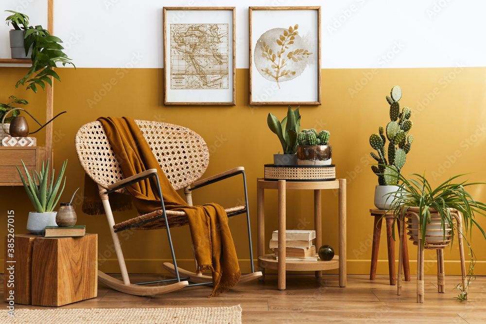 Fototapeta Stylish composition of living room interior with design rattan armchair, two mock up poster frames, plants, cube, palid and personal accessories in honey yellow home decor. Template.