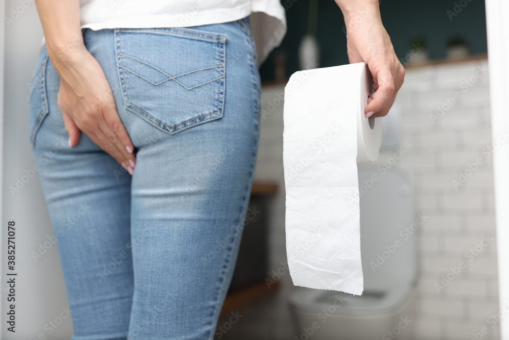 Fototapeta Woman holds hand on priest in other hand toilet paper and stands opposite the humiliated. Constipation and bloating concept